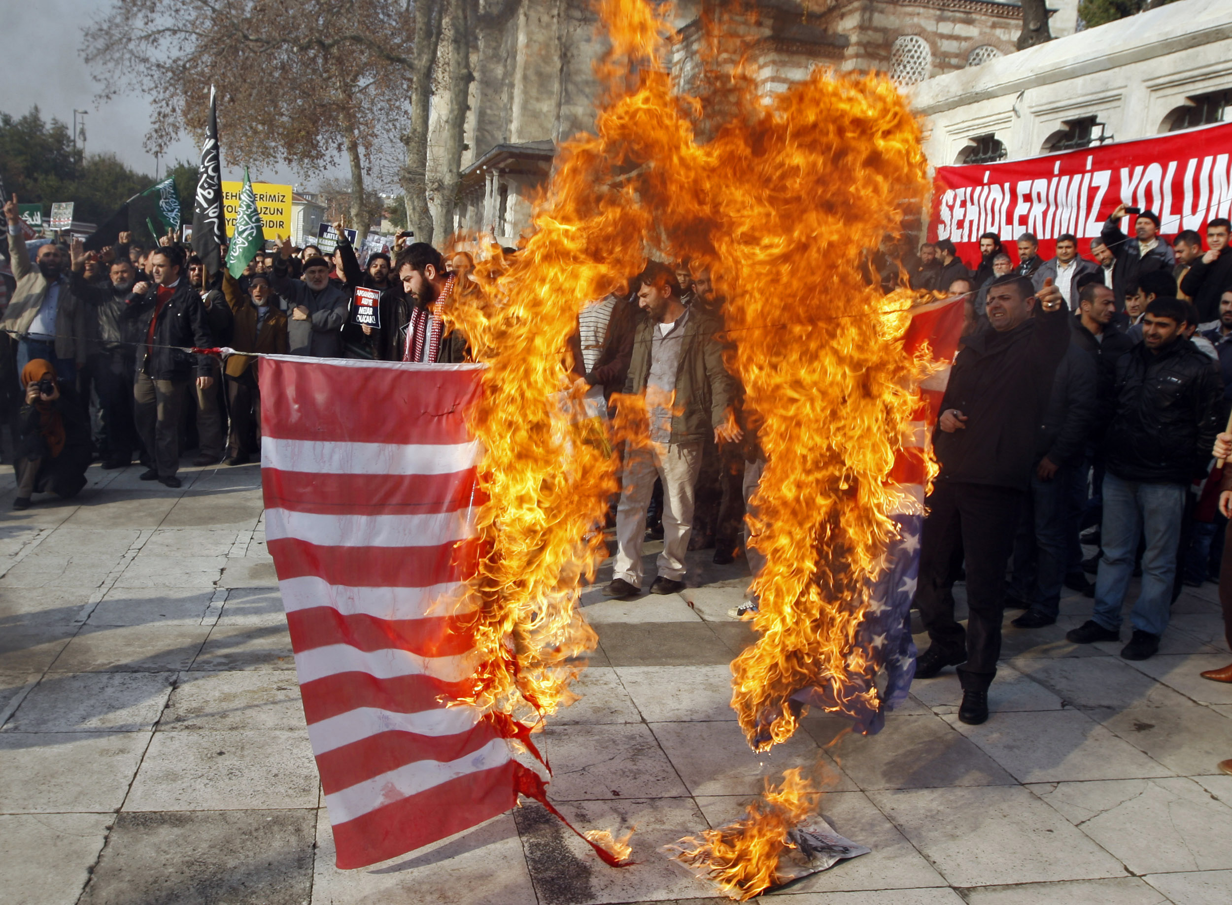 Protesters shout slogans as they burn a U.S. flag during an anti-America protest after Friday prayers in Istanbul December 2, 2011. REUTERS/Osman Orsal (TURKEY - Tags: POLITICS CIVIL UNREST)