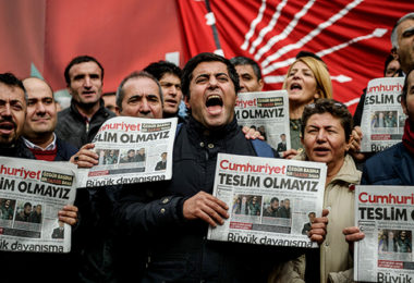 "TOPSHOT - Protesters hold copies of the latest edition of the the Turkish daily newspaper ""Cumhuriyet"" as they shout slogans during a demonstration outside the newspaper's headquarters in Istanbul on November 1,2016 a day after its editor in chief was detained by police.  Turkish police detained the editor-in-chief of the opposition newspaper Cumhuriyet, state media reported, while the daily said several of its writers were taken into police custody. Murat Sabuncu was detained while authorities searched for executive board chairman Akin Atalay and writer Guray Oz, the official news agency Anadolu said.  / AFP / OZAN KOSE        (Photo credit should read OZAN KOSE/AFP/Getty Images)"