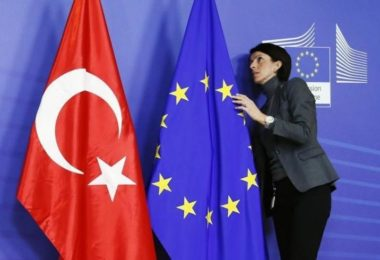A staff adjusts European Union and Turkish (L) flags ahead of the arrival of Turkey's Prime Minister Tayyip Erdogan (not pictured) at the EU Commission headquarters in Brussels January 21, 2014. REUTERS/Francois Lenoir