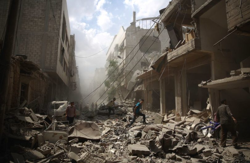 Syrians walk amid the rubble of destroyed buildings following reported air strikes by regime forces in the rebel-held area of Douma, east of the capital Damascus, on August 30, 2015. More than 240,000 people have been killed since Syria's conflict began in March 2011, and half of the country's population has been displaced by the war. AFP PHOTO / ABD DOUMANY        (Photo credit should read ABD DOUMANY/AFP/Getty Images)