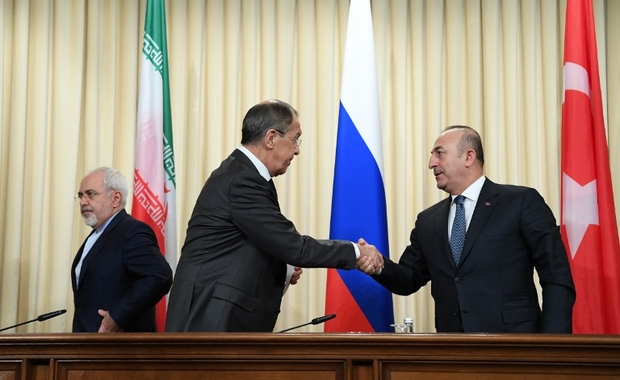 Russian Foreign Minister Sergei Lavrov (C) shakes hands with his Turkish counterpart Mevlut Cavusoglu (R) as Iran's Foreign Minister Mohammad Javad Zarif (L) looks on after a news conference in Moscow on December 20, 2016.   The foreign and defence ministers of Russia, Turkey and Iran are meeting in Moscow for key talks on the conflict in Syria. Iran and Russia are sharing a base in war-torn Syria to help coordinate their support for President Bashar al-Assad's forces, a top security official in Tehran said on December 20.   / AFP PHOTO / Natalia KOLESNIKOVA