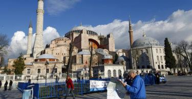 A tourist couple checks a map, near the Byzantine-era monument of Hagia Sophia, at Sultanahmet square in Istanbul,Turkey January 14, 2016. REUTERS/Murad Sezer - RTX22EU9